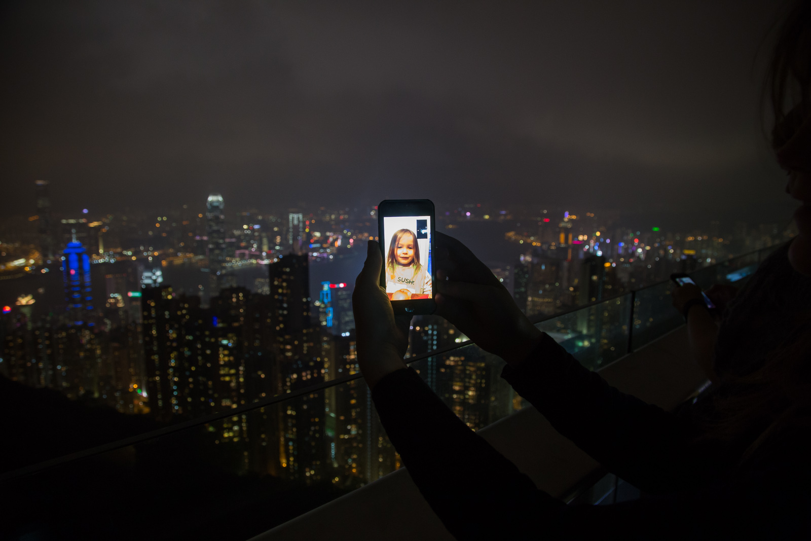 A child shown on facetime in front of the hong kong skyline at night