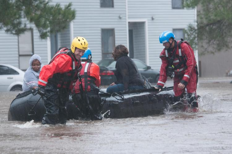 Rescue workers in water up to their knees pulling a boat with people behind them.