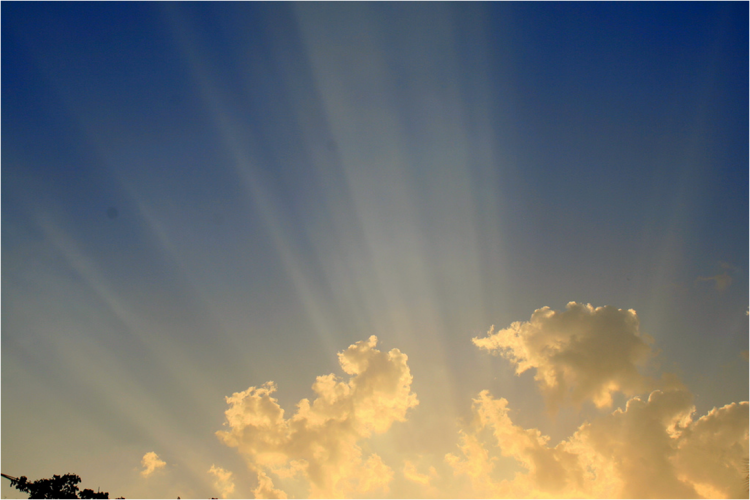 a cloud with rays of sun extending through, backdrop of blue sky