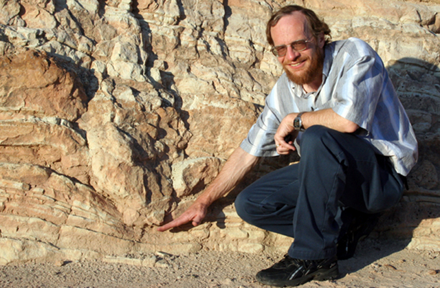 Dr. Alley standing next to an edge-on  dinosaur track.