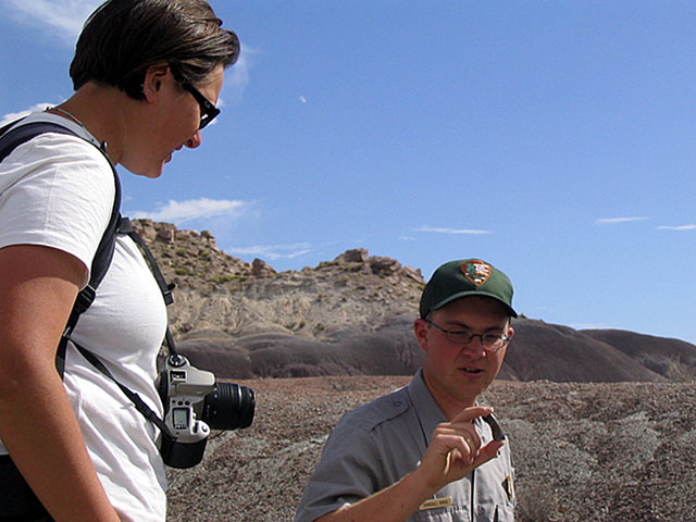 Paleontologist showing a student a still-sharp fossil tooth.