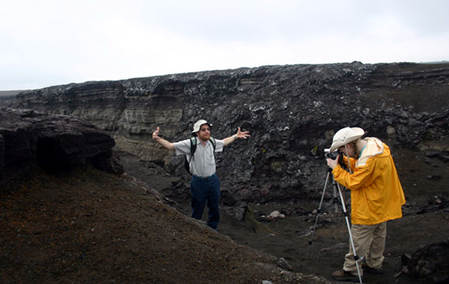 a person filming Dr. Alley as he stands in a rift (walls of rock on either side)