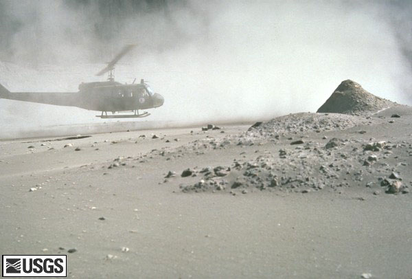 Volcanic ash covering the landscape around the volcano.  A helicopter is hovering near the ground.