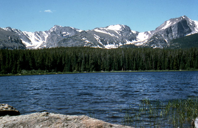 Mountain peaks with small glaciers rise above Bierstadt Lake