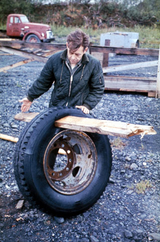 Man holding a large tire with a two by four sticking straight through the rubber part of the tire.