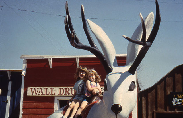 Children sitting on jackalope statue at Wall Drug tourist area in Badlands