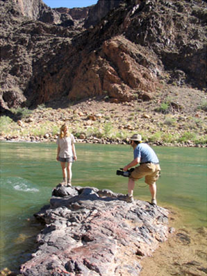 A young woman and a man with a video camera standing on a rock in the river, at the bottom of the Grand Canyon