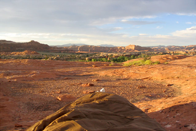 Sunrise at Needles area campground in Canyonlands with foot of sleeping bag in foreground
