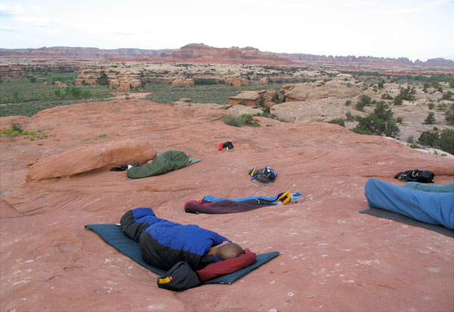 Several students in sleeping bags on the rocks at Needles area campground, Canyonlands