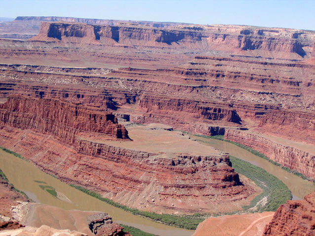 Panoramic view of Canyonlands and a muddy Colorado River with exposed sandbars, viewed from Dead Horse Point State Park