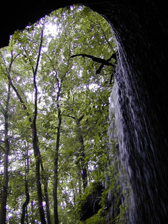 View looking out of Mammoth Cave with waterfall to the right of entrance and green forest straight ahead