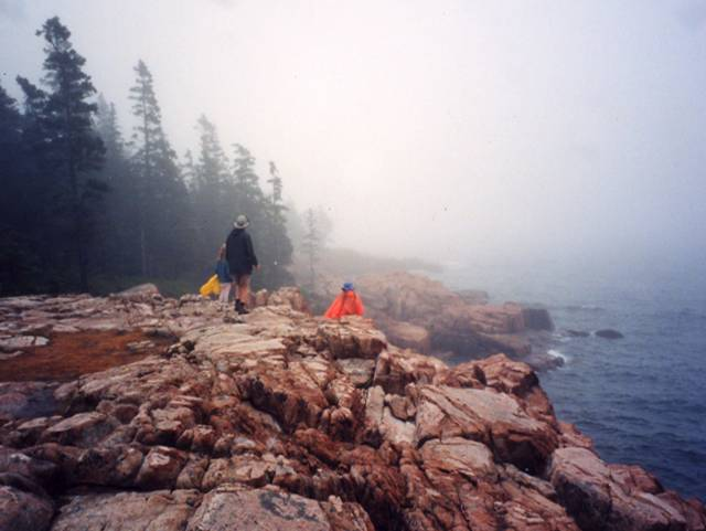 People standing on rocks at the coast.  Raining and foggy. Acadia National Park