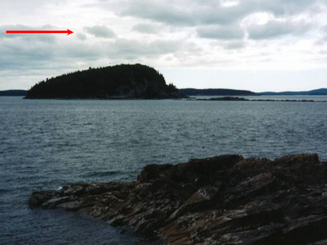 Body of water with island in center. Cloudy skies. Arrow at top left points to the right, indicating direction of ice flow