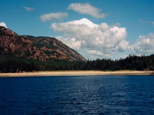 Beach at Acadia with water in foreground, mountains and cloudy skies in background