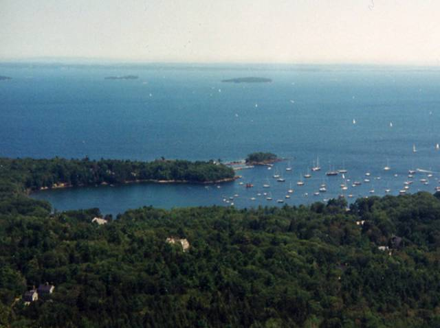 Ocean with inlet and forested land in foreground, small islands in the distance.  Sailboats anchored in the inlet and sailing in the distance