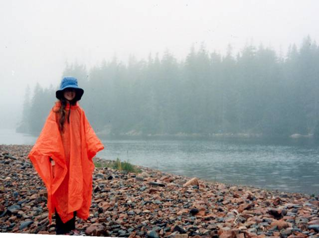 Person standing in the rain on rocky beach, wearing orange rain poncho and blue rain. Water and Evergreens in the background