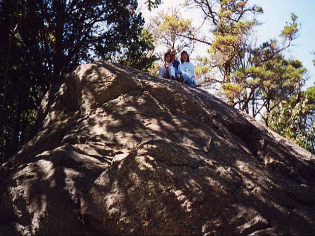 Family of three sitting atop Great Rock