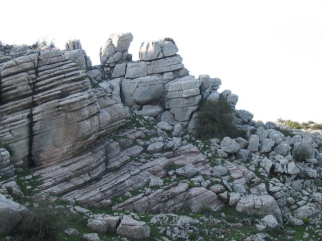 Limestone formations in the Torcal de Antequera. Rock piles with many parallel and slightly sloped horizontal line