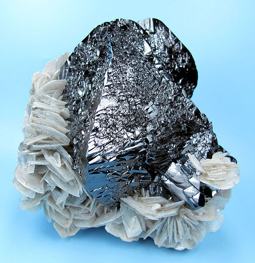 Cassiterite, grey reflective rock with white feathery plate like other rocks on it