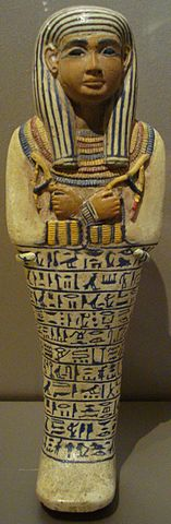 sculpture of Egyptian woman in headdress with arms crossed