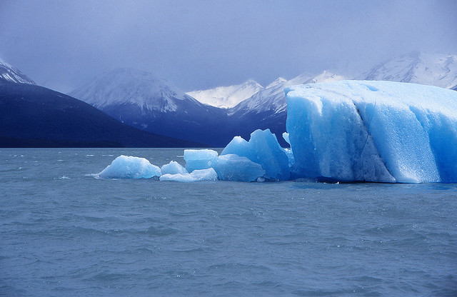 Glacier in a bay surrounded by mountains. Glacier has blue color.