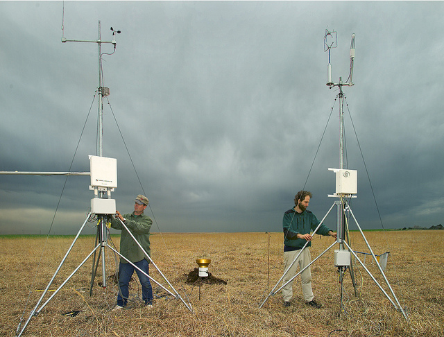 two men setting up anemometers in the field