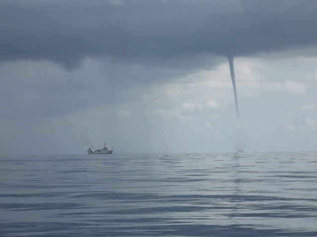 water spout over water next to boat