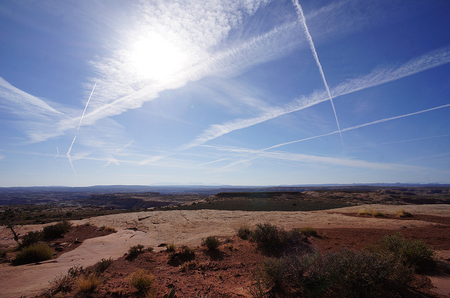 contrails in a blue sky over desert