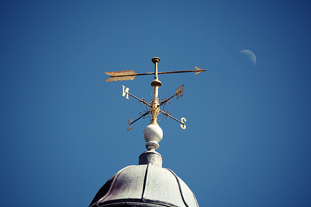 weathervane on top of building with moon and blue sky behind