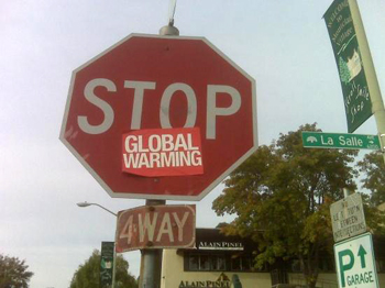 Image of a stop sign with a red global warming sticker on it