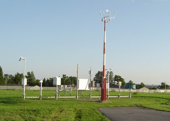 A collection of weather instruments alongside of a runway