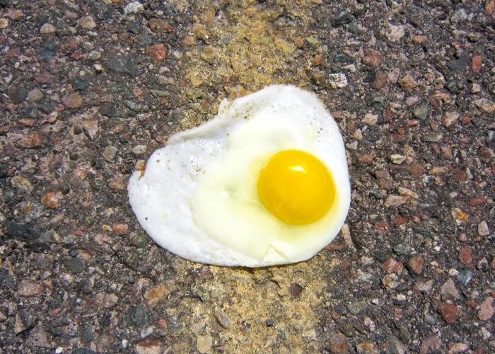 Fried egg on an asphalt surface.