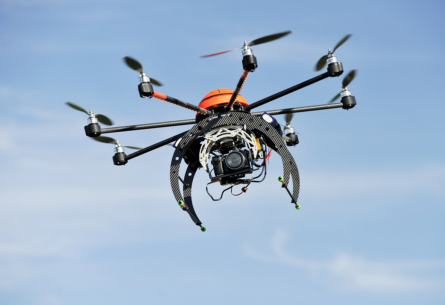 Picture of an unmanned aerial vehicle designed for mapping. Looks like a miniature helicopter with a camera attached.