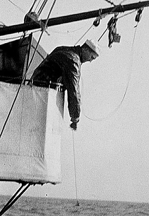 Black and withe photo from 1916 of a Seaman paying out a sounding line during a hydrographic survey